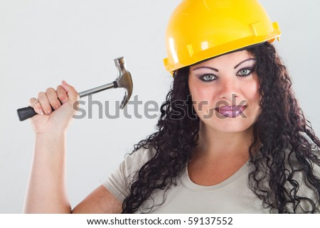 female plus size model wearing construction helmet and holding a hammer - stock photo