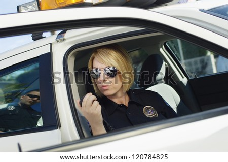 Female police officer communicating on walkie-talkie while sitting in car - stock photo