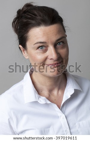 female portrait - portrait of a gorgeous elegant mature woman with smart white shirt smiling for fun and wellbeing, grey background - stock photo