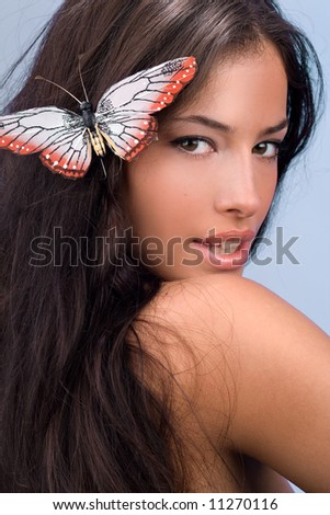 female portrait with butterfly in hair, studio shot - stock photo