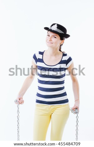 Female posing as police officer holding chains  - stock photo