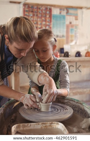 Female potter assisting girl in pottery workshop