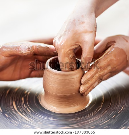 Female Potter creating a bowl on a Potters wheel, the master potter helping her - stock photo