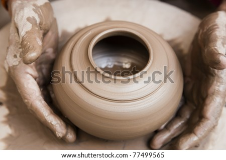 female potter's hands shaping up the terracotta clay pot on wheal. - stock photo
