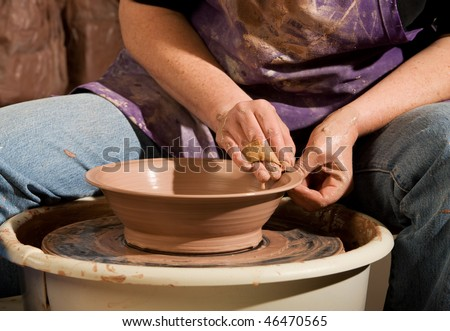 Female Potter Shaping Clay on Wheel in Studio