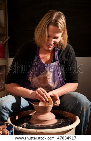 Female potter working with clay on wheel in studio - stock photo