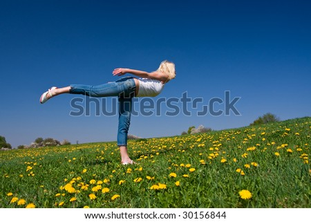 female practicing yoga on a flowery meadow
