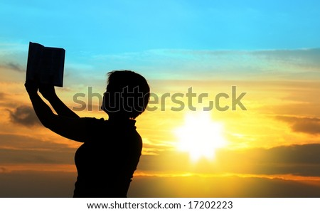 female praying with bible against summer sunset, person isn't identifable - stock photo