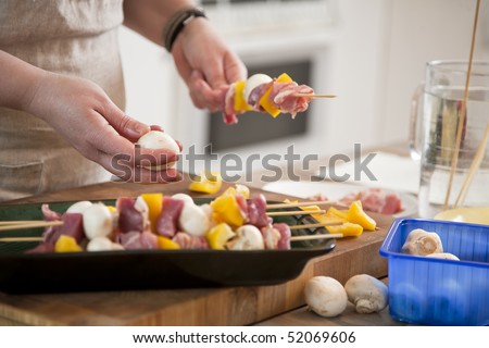 Female preparing meat and vegetables for barbeque - stock photo