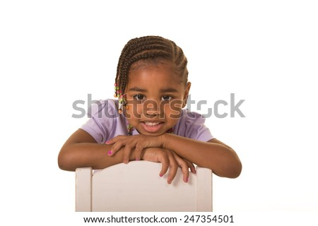 Female preschool child sitting in a chair isolated on white