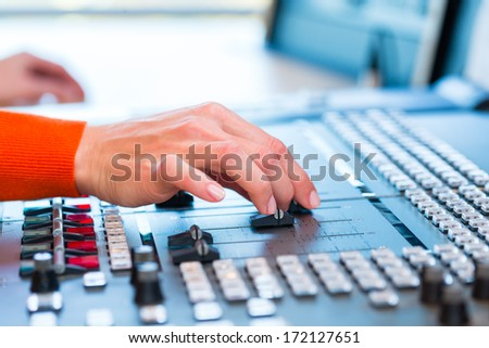 female Presenter in radio station hosting show for radio live in Studio - stock photo