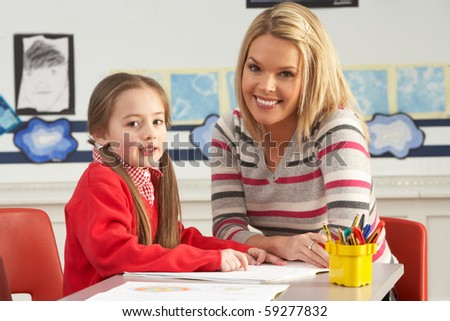 Female Primary School Pupil And Teacher Working At Desk In Classroom - stock photo