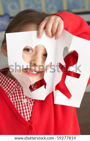 Female Primary School Pupil Cutting Out Paper Shapes In Craft Lesson - stock photo