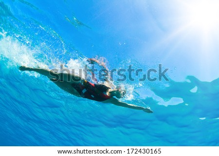 Female professional swimmer gushing through blue Red sea water with bubbles