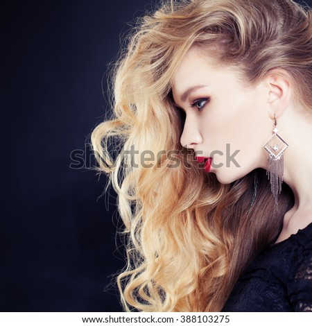 Female Profile. Beautiful Woman with Long Wavy Blonde Hair on Dark Background - stock photo