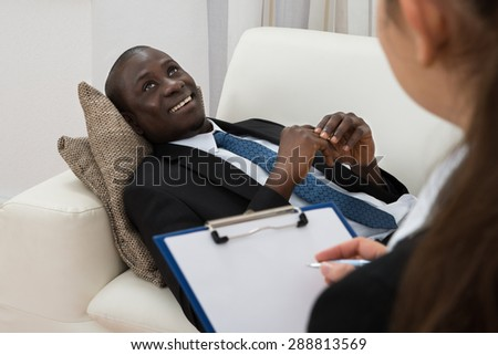 Female Psychiatrist Making Notes In Front Of Patient During Psychological Therapy Session - stock photo