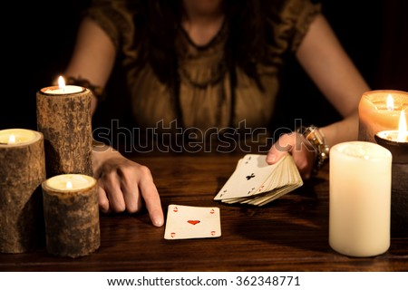 Female psychic is telling the future with playing cards, concept tarot and numerology - stock photo