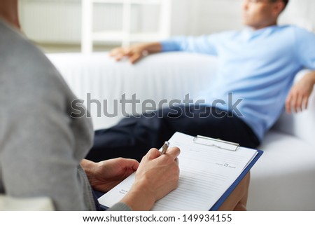 Female psychologist making notes during psychological therapy session - stock photo