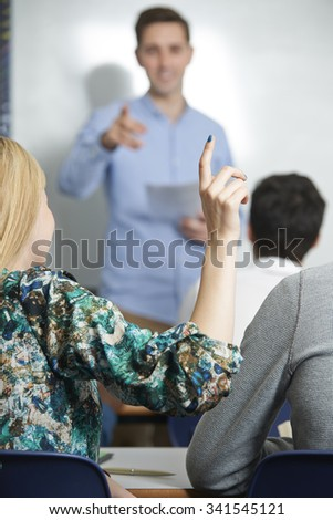 Female Pupil Answering Question In Class - stock photo