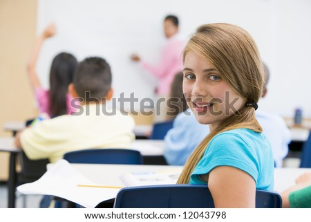 Female pupil in elementary school classroom - stock photo