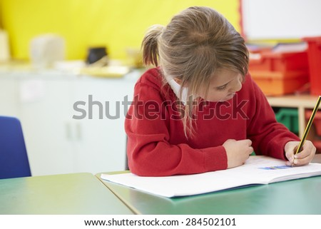 Female Pupil Practising Writing At Table - stock photo