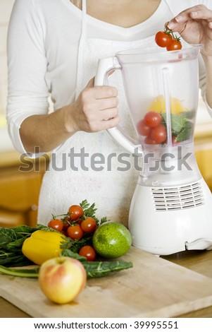 female putting vegetables in blender - stock photo