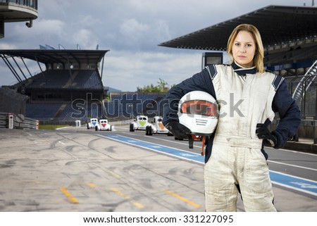 Female race car driver, holding her helmet under her arm, standing in the pits lane of a race track circuit - stock photo