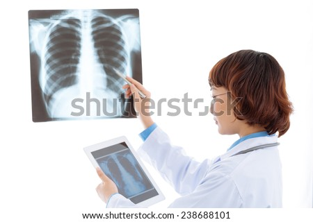 Female radiologist comparing chest x-ray with an image on the digital tablet - stock photo