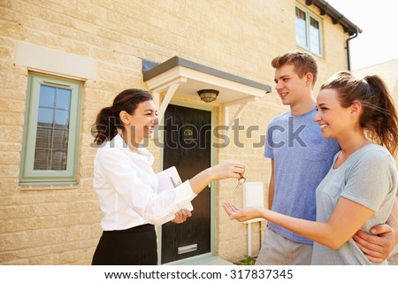 Female real estate agent giving keys to new property owners - stock photo