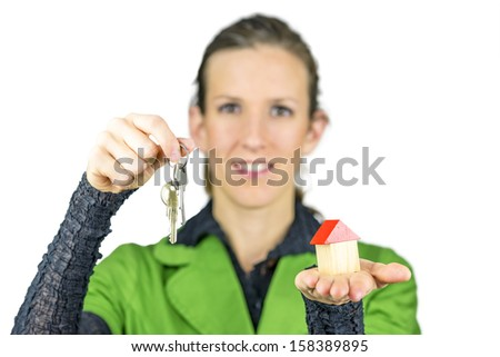 Female real estate agent holding house keys in one and wooden toy house in the other hand. Isolated over white background. - stock photo