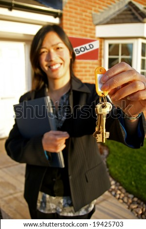 Female real-estate agent holding keys to a new property - stock photo