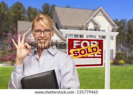 Female Real Estate Agent in Front of Sold Home For Sale Sign and House. - stock photo