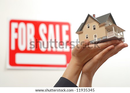 Female real estate agent's hands offering a home for sale - stock photo