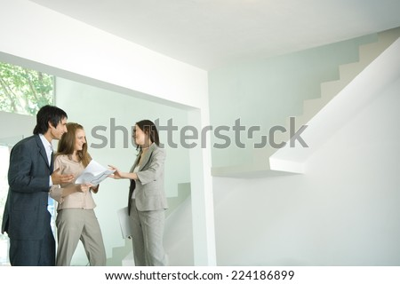 Female real estate agent showing house to young couple, pointing to blueprints - stock photo