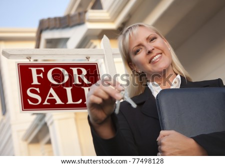 Female Real Estate Agent with Keys in Front of Sign and Beautiful House. - stock photo