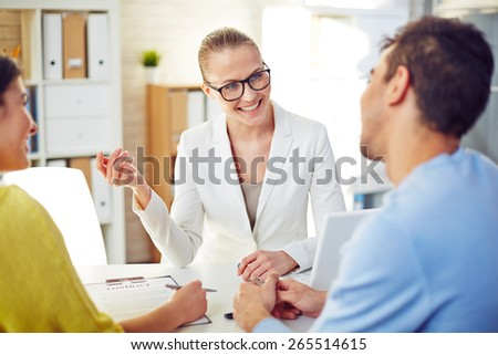 Female realtor explaining young couple terms of contract - stock photo
