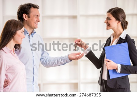 Female realtor is giving to young couple a key from new flat. - stock photo