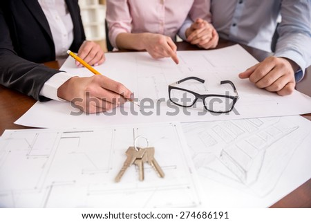 Female realtor showing contract with floor layout in an apartment to a young couple. - stock photo