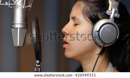 Female recording artist recording a song in the studio - stock photo