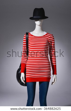 female red clothes in jeans with bag on a mannequin-light background    - stock photo