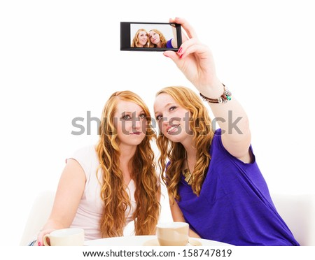 female redhead friends making photos of themselves on white background - stock photo