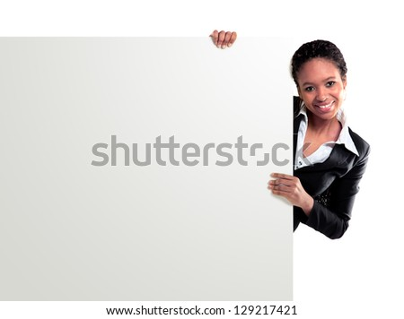 Female representative pointing towards placard and smiling at camera - stock photo