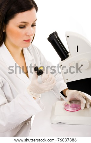 Female research scientist in lab coat and rubber gloves looking at specimen under microscope in laboratory - stock photo