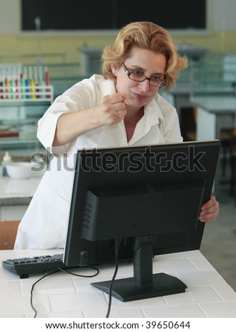 Female researcher angry with her computer in the laboratory.