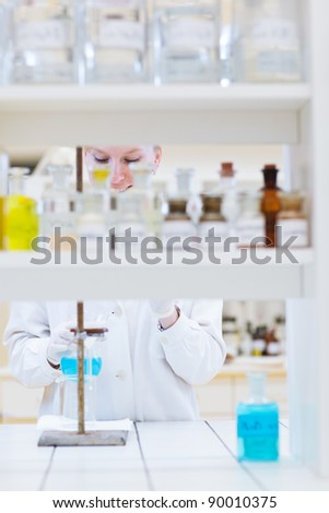 female researcher/chemistry student carrying out research in a chemistry lab (color toned image; shallow DOF) - stock photo