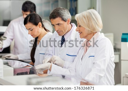 Female researcher discussing with colleague in laboratory - stock photo
