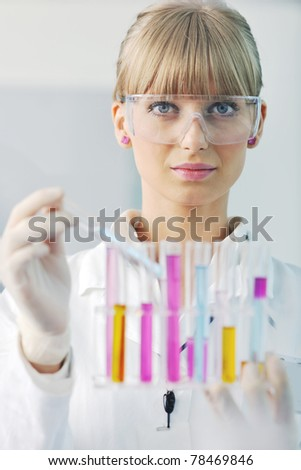 female researcher holding up a test tube in lab - stock photo