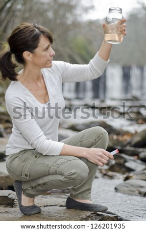 Female researcher testing the water quality in a river - stock photo