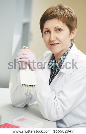 Female researcher with dropper of medicine during pharmaceutical laboratory blood test examination - stock photo