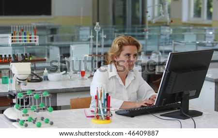 Female researcher working on a computer in a laboratory. - stock photo